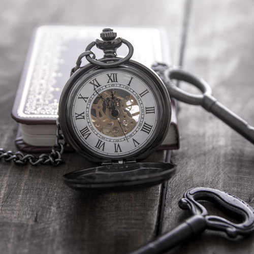 pocket watch on grunge wooden table, close up